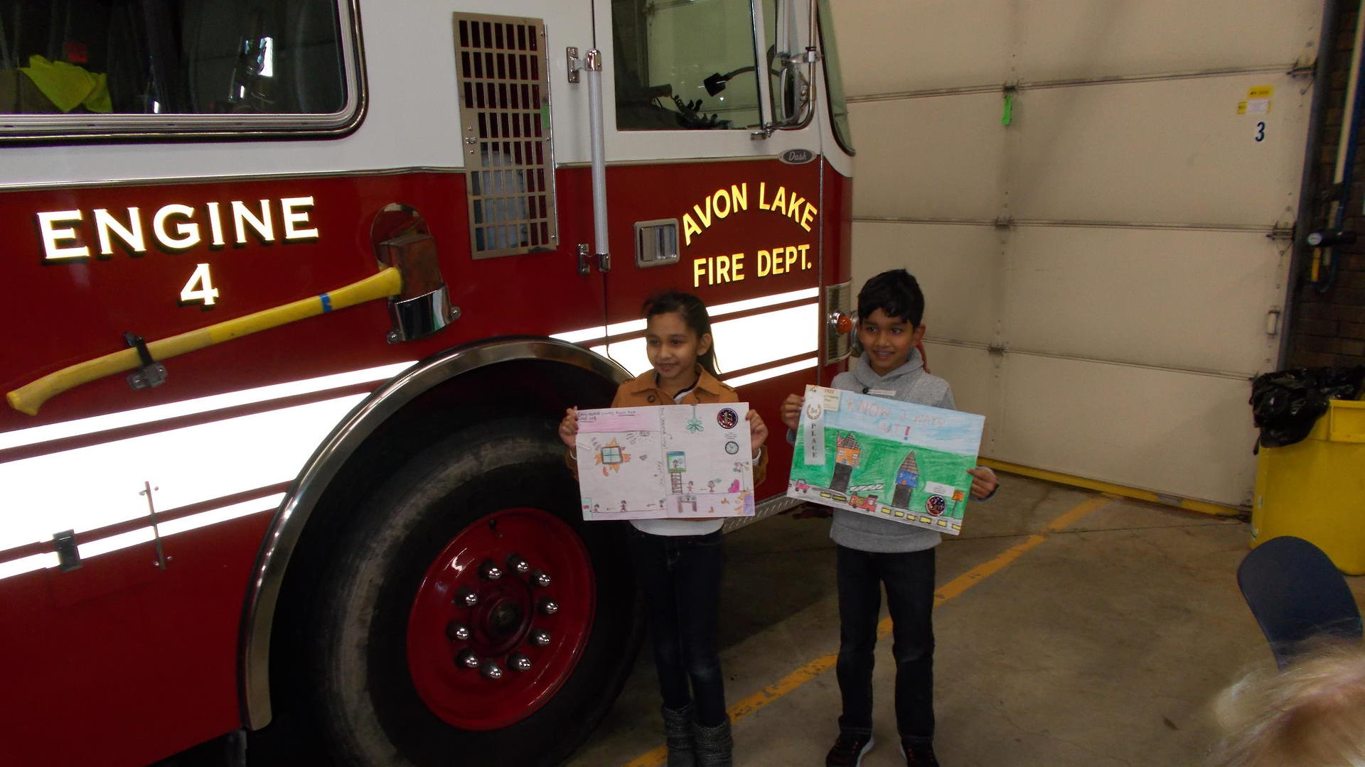 two children holding their posters which won a trip to the fire house in Avon Lake