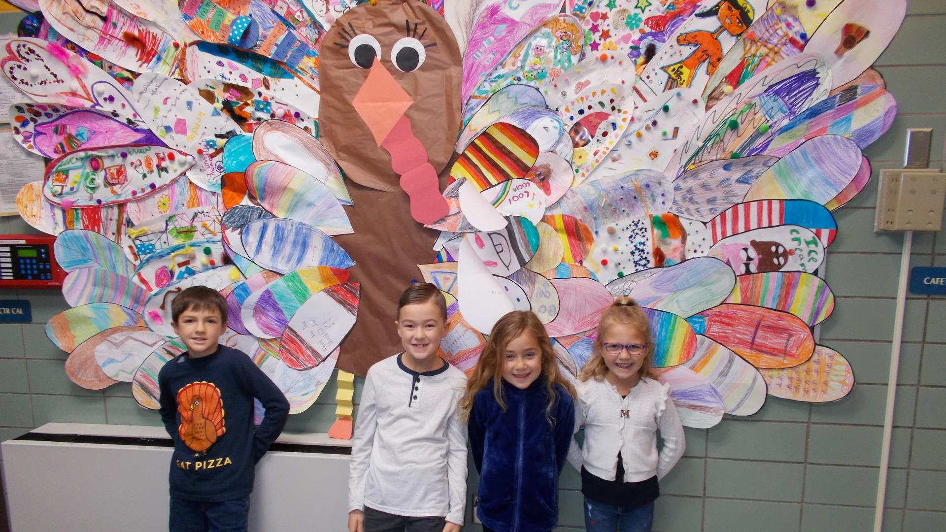 Students standing in front of a bulletin board for Thanksgiving