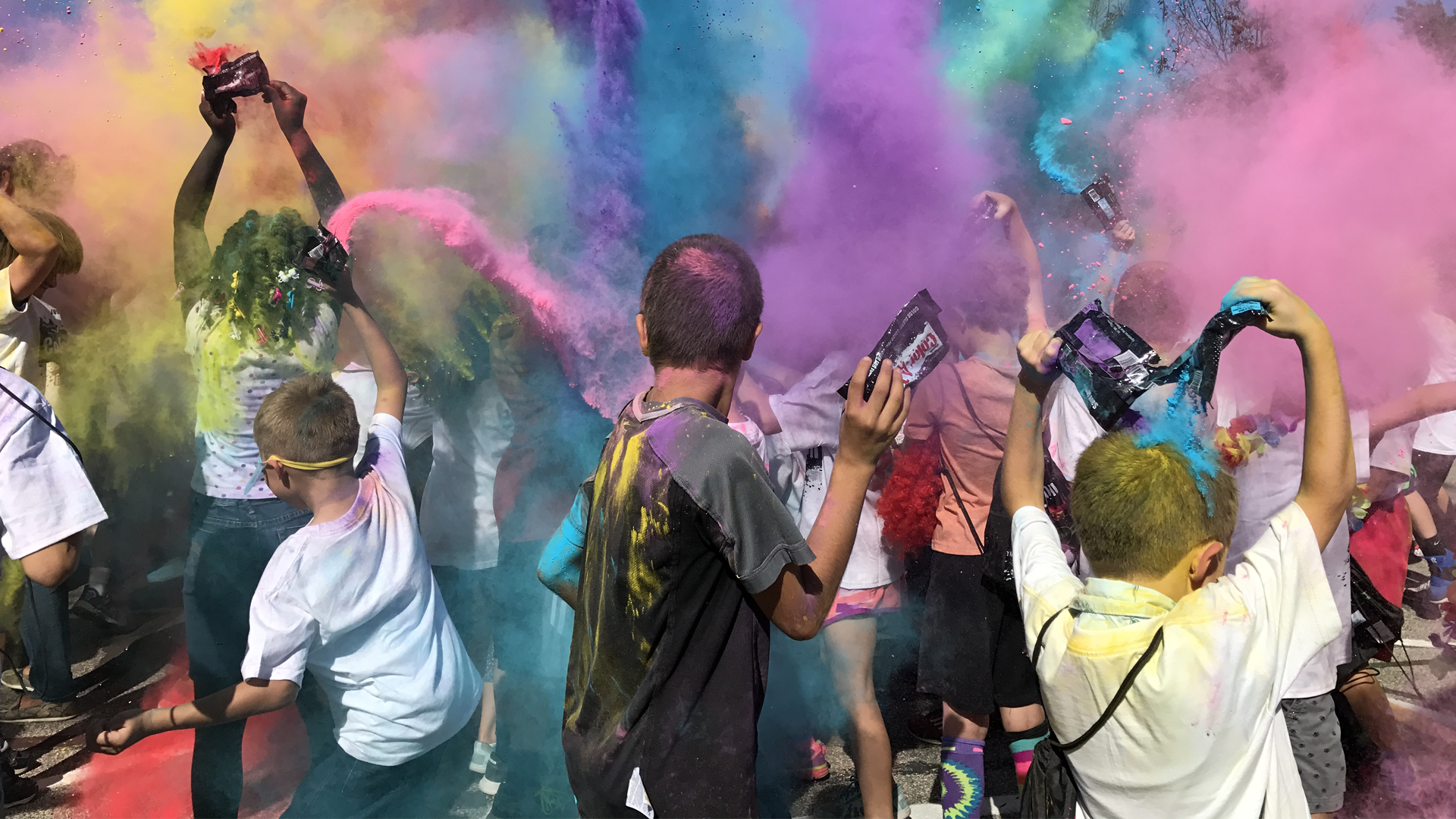 Students throwing color dust