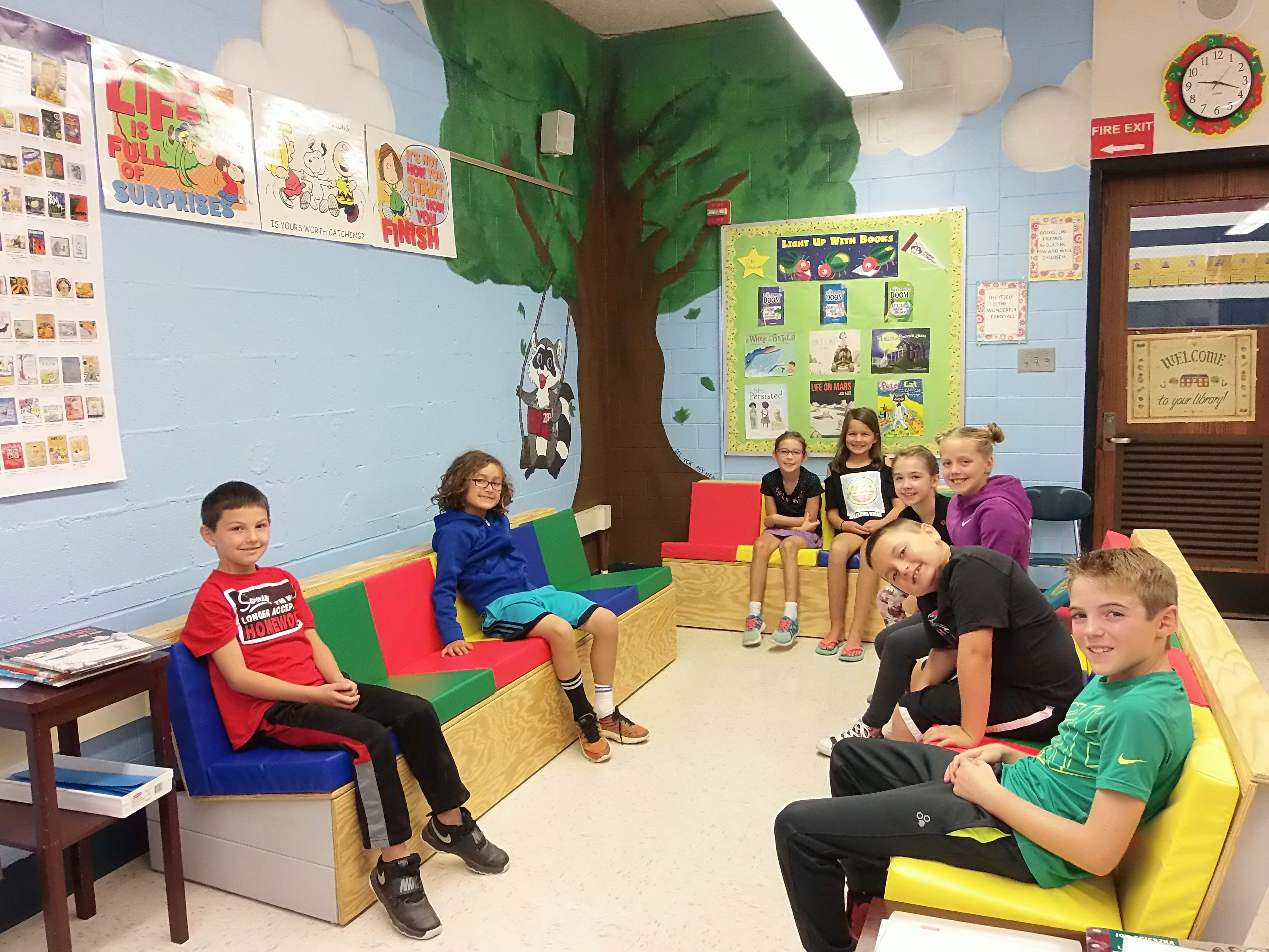 3rd graders enjoying the new mural and seating in the library.