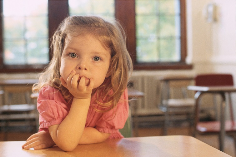 Young girl looking with elbow on desk and chin on hand